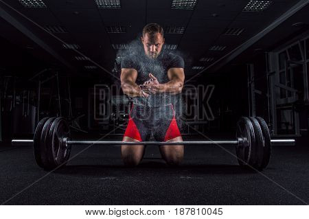 Ahlete Kneels In The Gym And Claps His Hands After Which The Dust From The Chalk Flies
