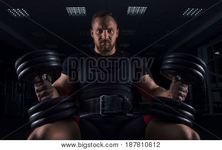 Impressive Athlete Sits On A Bench With Two Dumbbells On His Legs