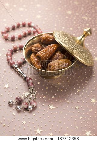 Arabian dates in a small bowl and rosary. Ramadan festival background.