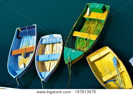 Colorful rustic row boats tied to a dock at a marina