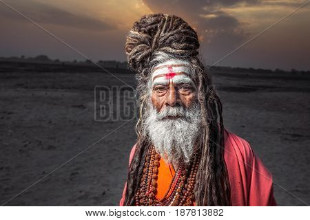 Portrait of sadhu standing with sunrise behind him, Varanasi, India.