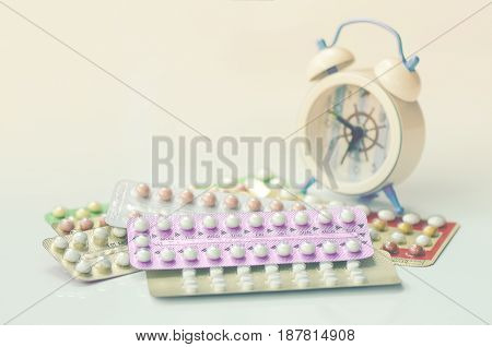 Oral Contraceptive Pills With Alarm Clock Background.
