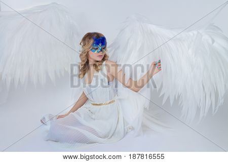 beautiful young model with big angel wings sitting in the studio wearing blue venecian carnival mask. white background.