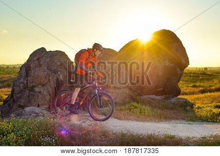Cyclist Riding the Mountain Bike on the Trail near the Beautiful Rocks at Sunset. Extreme Sport Concept.