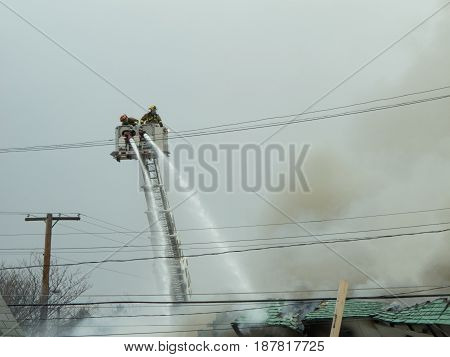 LIVONIA MICHIGAN - March 19 2013. Two fire fighters atop an aerial ladder train their hoses on the roof of a burning building in a valiant effort to save to save a burning building.