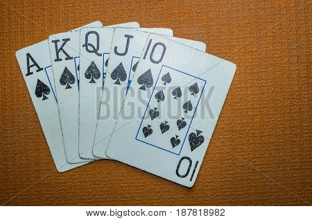 A set of well loved cards laid out in a royal flush.