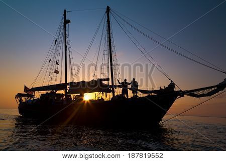 Gaff rigged schooner silhouette in the setting sun
