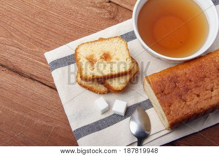 Black tea with sugar and cake with jam on a napkin and on a wooden background. There is room for text