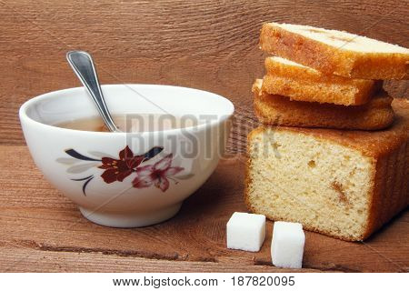 Black tea with sugar and cake with jam on wooden background