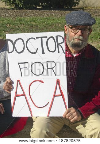 Asheville, North Carolina, USA - February 25, 2017: An older man holds a sign at an Affordable Care Act rally that says