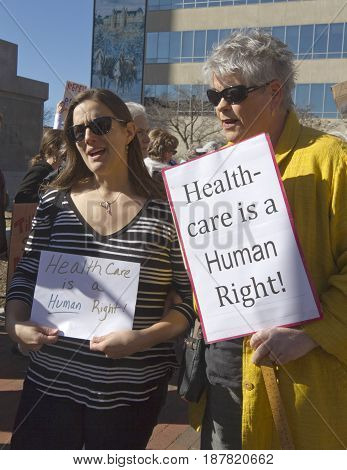 Asheville, North Carolina, USA - February 25, 2017: Women hold signs at an Affordable Care Act rally saying