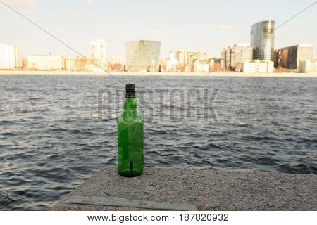 The Problem Ecology- Garbage: On The Waterfront Stands A Green Bottle Of Beer With A Cigarette Butt
