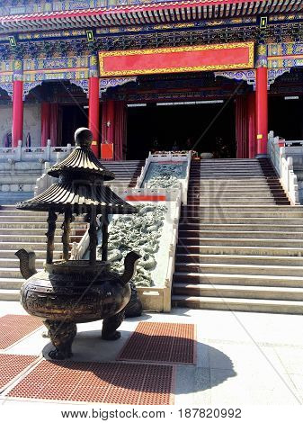 Big Brass Joss Stick Pot or Chinese Incense Burner in Front of The Stair Step at Buddhist Temple.