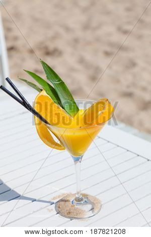 Exotic summer drink standing on deckchair sandy beach in background