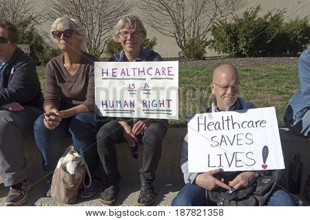 Asheville, North Carolina, USA - February 25, 2017: Older Americans hold signs at an Affordable Care Act rally saying