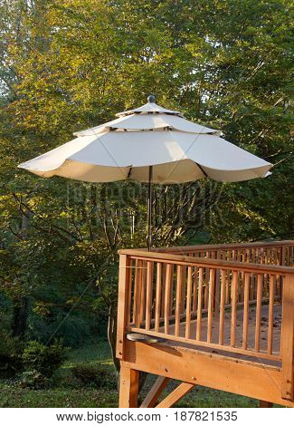 raised wood deck and umbrella in a forested setting on a sunny day in early autumn