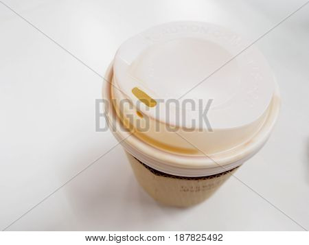Close-up detail of the top of a disposable paper cup plastic lid and cardboard sleeve with droplets of coffee on its edge and rims. White background. Drinks and cafe concept.