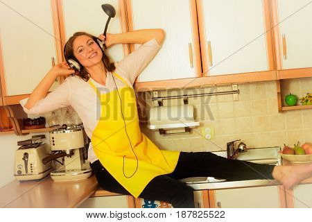 Relax in kitchen. Listening music. Funny happy housewife cook chef with earphones wearing yellow apron sitting and relaxing at home.