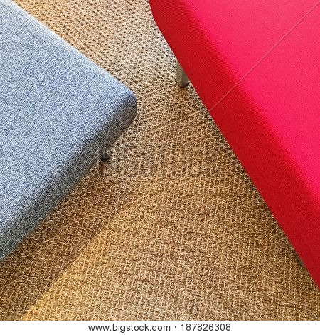 Red and gray seats on carpet floor. Modern furniture.