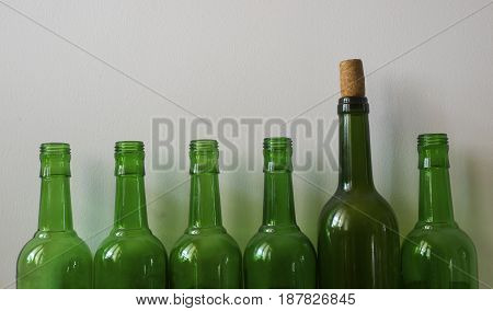 Neatly lined up a lot of empty wine bottles under the background of white walls.