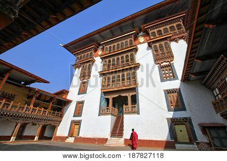 Monk walking in Paro Rinpung Dzong Buddhist monastery and fortress on a hill near the Paro Chu river. Bhutanese style building decorated with carved wood window frames inside the ancient Rinpung Dzong Paro Bhutan.
