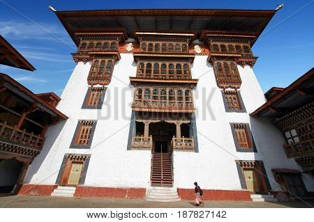 Woman in traditional Bhutanese dress walking in Paro Rinpung Dzong Buddhist monastery and fortress on a hill near the Paro Chu river. Bhutanese style building decorated with carved wood window frames
