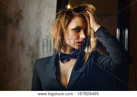 Young attractive girl in a jacket and bow tie. Femme fatale. Evening makeup smokey eye. She straightens her hair. Passion and desire. A languid look