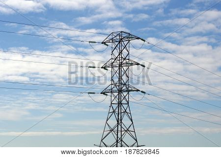 High voltage power lines with blue sky and clouds.
