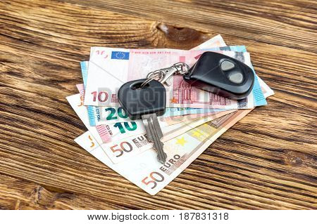 Car key with remote control and euro bills on the table.