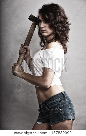 Sex equality and feminism. Sexy girl holding hammer tool. Attractive woman working as repairman or mechanic.