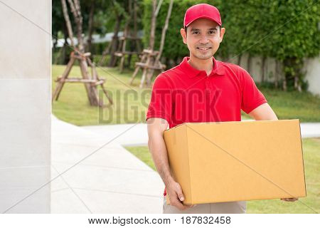 Delivery man in red uniform holding parcel box