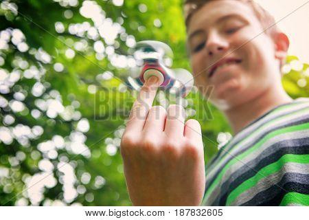 Teen boy with a fidget spinner outdoors