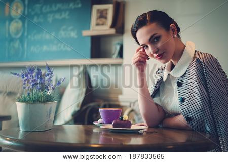 Elegant young lady alone in a cafe