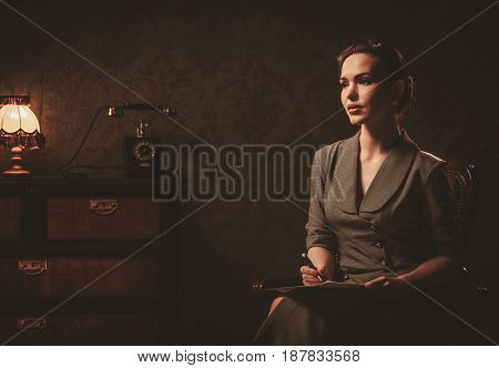 Beautiful woman composing letter in retro interior