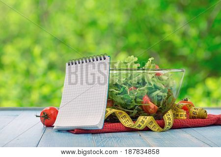 Blank notebook with large bowl of salad and measuring tape on blue wooden table close up against background of green bokeh leaves