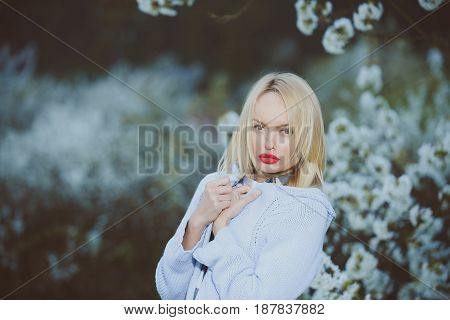 Blonde Woman With Make Up On Red Lips In Flowers