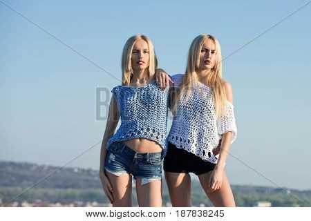 Twin sisters sexy girls or cute women stylish female models with long blond hair in fashionable knitted tops and shorts posing on sunny day on blue sky. Idyllic summer vacation. Family