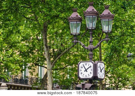 Paris France - May 2 2017: The ancient light pole with the watches on a green garden background on May 2 2017 in Paris France.