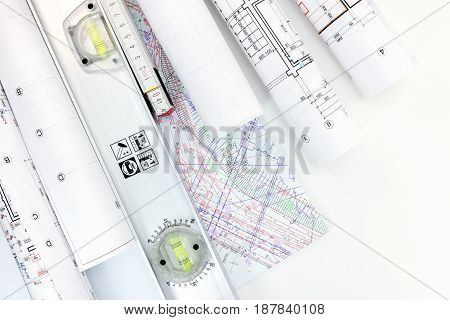Architect Workplace With Rolls Of Construction Blueprints, Plans And Spirit Level