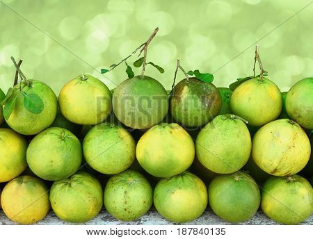 Grapefruit or pomelos fruit with leaves on green bokeh background