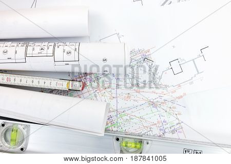 Spirit Level And Zigzag Ruler With Rolls Of Construction Blueprints On Architect Workplace