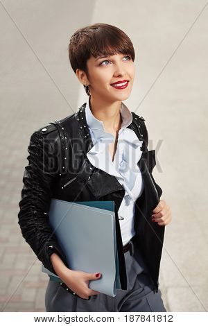 Happy young fashion business woman with a folders walking in city street. Stylish female model in black leather jacket