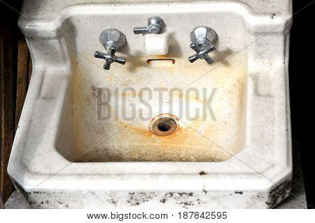Old fashion dirty and rusty wash basin left in a bathroom.