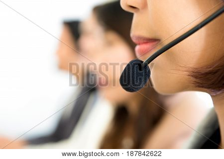 Woman lower face with microphone headset in call center - side view