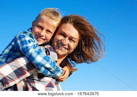 Beautiful mum with cute little child on her back. Parent and child smile and looking to camera. Closeup.