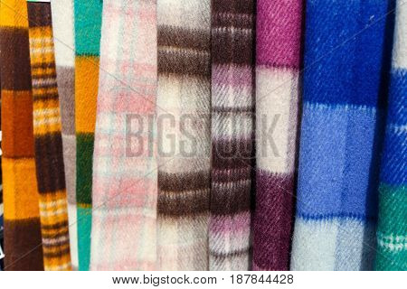 Wool blankets and plaids on the stand in the bed-clothes store