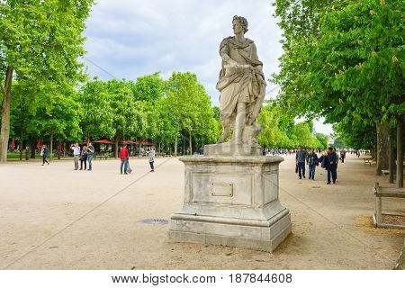 Paris France - May 2 2017: Julius Caesar statue in the Garden of the Tuileries with a crowd on May 02 2017 in Paris France.