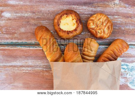 Bakery products in paper bag on table. Top view.