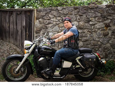 Kiev Ukraine May 8 2017: The biker sits on a motorcyclein the yard of his house.