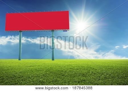 Red billboards on green field and sky background.
